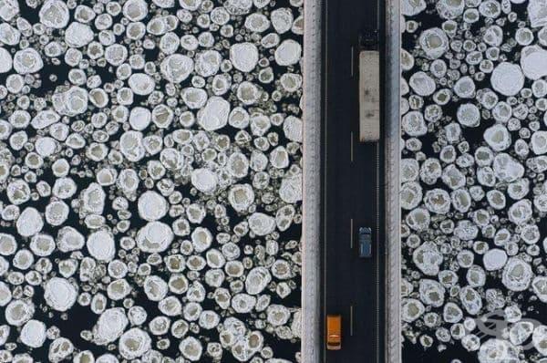 Изглед отгоре на мост над замръзнала вода.