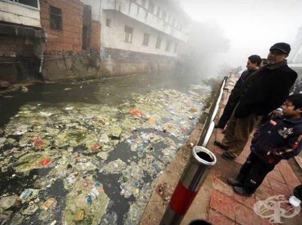 Хора, които гледат една от най-замърсените реки в град Жугао, Китай.