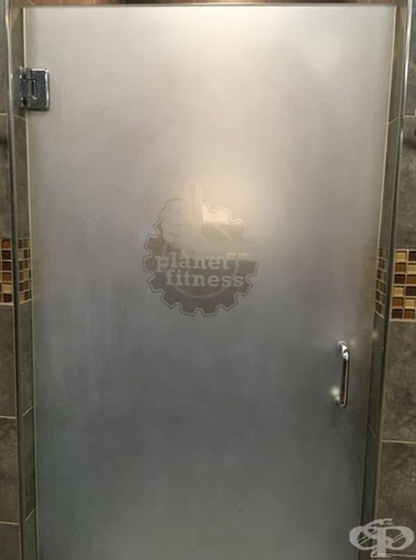 Врата към дамската баня във фитнес зала, на която е поставено логото на фитнеса на нивото на гърдите на жените.