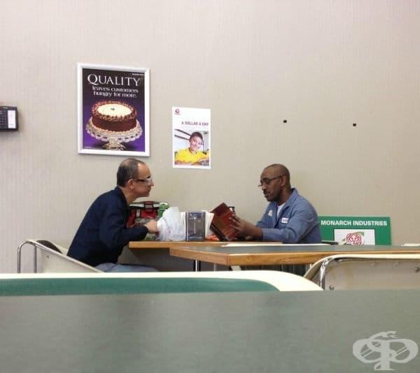Мъж чете книга на свой колега по време на обяд, защото той не може.