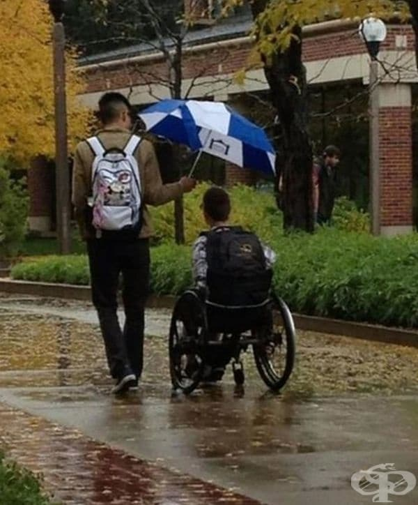 Младо момче държи чадъра си над младежа в количката, за да го предпази от дъжда.
