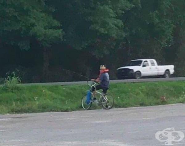 Този мъж лови риба върху колелото си в празно езеро. Той е със спасителна жилетка и корона.