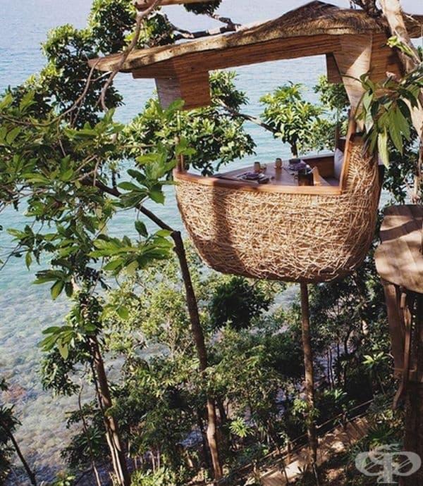Ресторант на Soneva Kiri Eco Resort, Тайланд, при който масите са позиционирани на дървета.