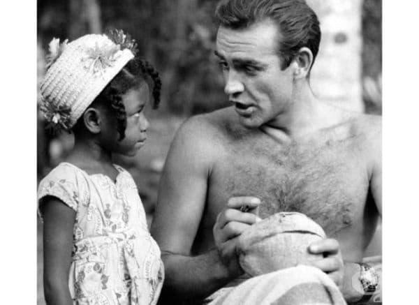 """Шон Конъри подписва кокосов орех за дете от Ямайка по време на заснемането  на """"Доктор Но"""", 1962."""