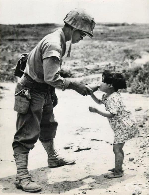 Този американски морски пехотинец дава вода на японско момиче, което открива в пещера (1945, Окинава).