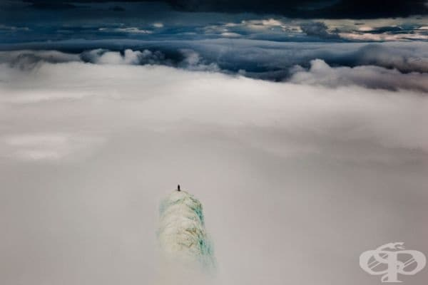 Алпинист, качен на върха на планина в Исландия.