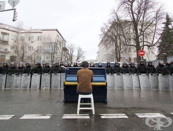 Маркиан Мацек свири на пиано за полицията в разгара на украинската революция.