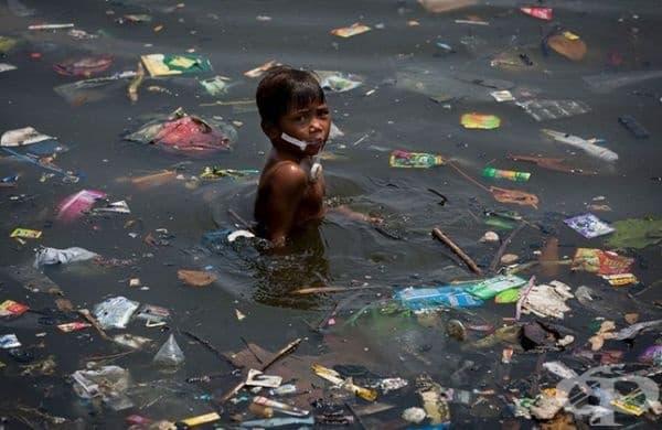 Момче плува в река с множество пластмасови отпадъци.