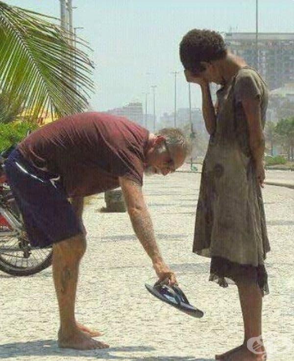 Този мъж дава своите обувки на непривилегирован тийнейджър.