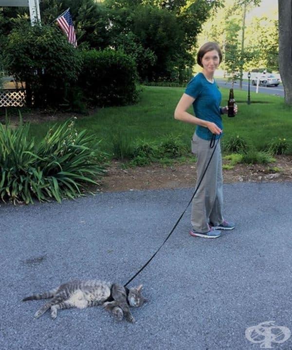 Жената е решила да се поразходи, но котката е на друго мнение.