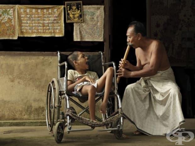 Бали. Мъж свири на флейта от бамбук, за да разсмее сакато момче, което обича като собствен син.