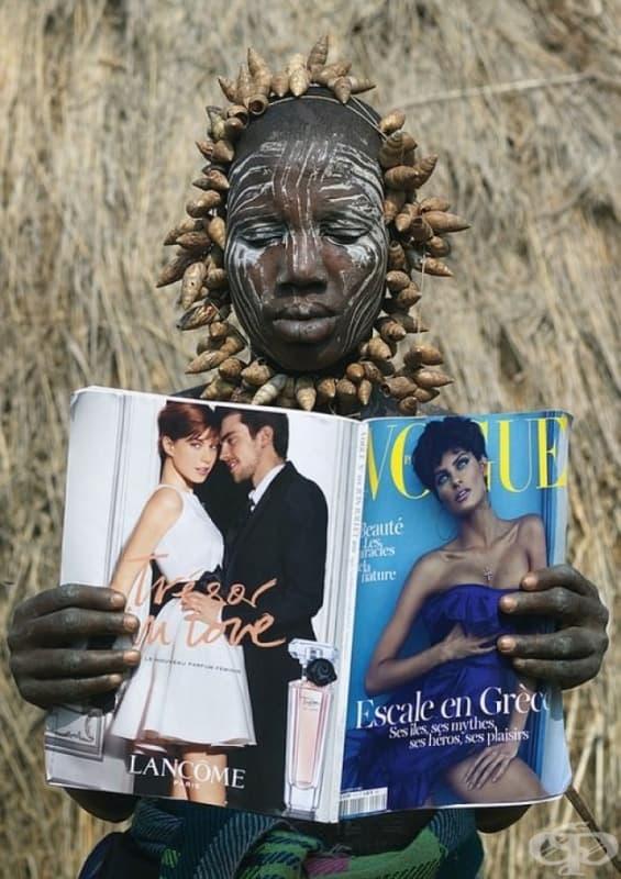Жена от племето Мурси от Етиопия разглежда списание Vogue за първи път.