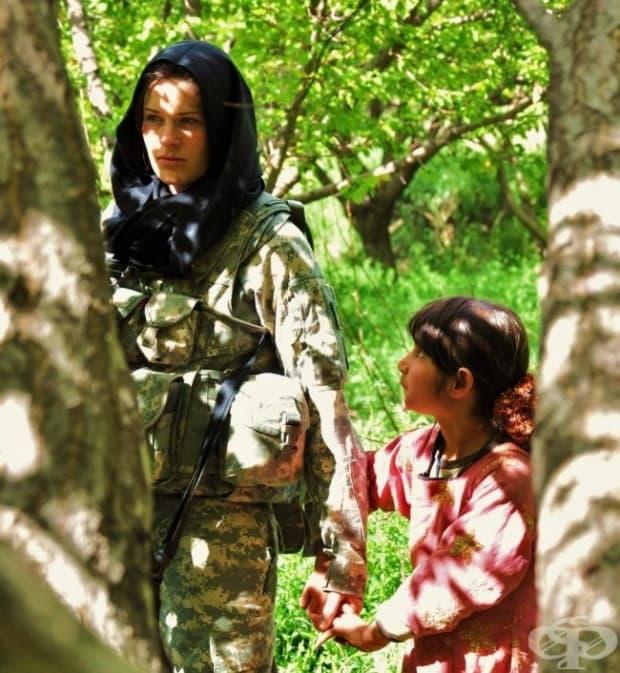 Афганистан. Малко момиченце държи за ръката американски войник.