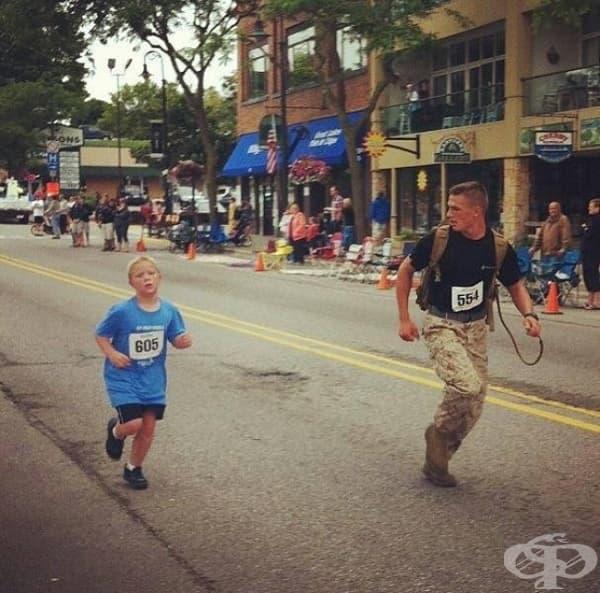 Войник тича с момче, което е изостанало от основната група по време на маратон.