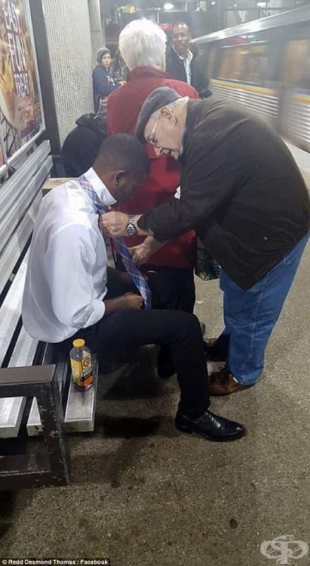 Възрастен човек помага на млад момък с вратовръзката.