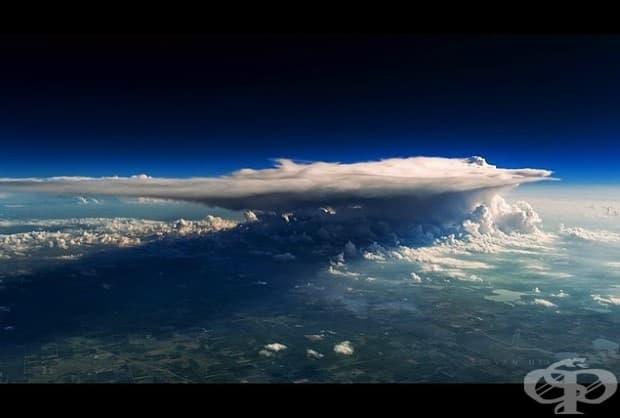 Буря над Минесота. Огромен купест облак над щата Минесота в САЩ. Бурята е толкова силна, че изсмуква въздух от земята и го забива в горните слоеве на атмосферата, както можете да видите тук, докато повечето облаци са засмукани към центъра на облака.