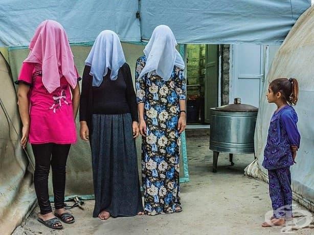 Момиче гледа към три кюрдски жени със скрити лица. Две от жените споделят, че са били принудени да се оженят за бойци на ISIS, преди да избягат към бежански лагер.