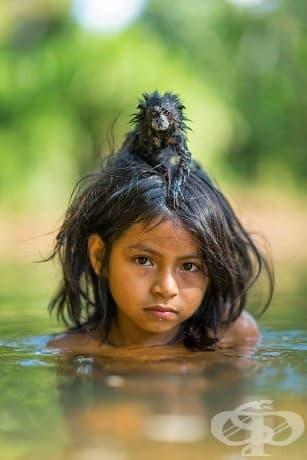 Момиче се потапя в река Yomibato, дълбоко в Националния парк на Перу - Ману.