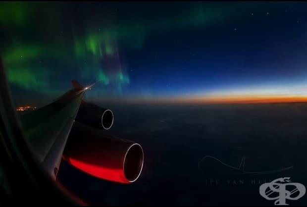 Северното сияние преди изгрев.  Светлинното шоу на Северното сияние, докато слънцето бавно осветява небето на изток, с изглед към крилата и двигателите на боинг 747-400.