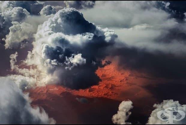 Облаци над Сахара. Облаци над необятната и привидно безкрайна Сахара. Червено / оранжевото сияние на огромните пясъчни дюни и равнините проблясва през облаците, само за да покаже контраста между екстремната суша по-долу и огромното количество вода горе в