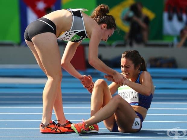 Ники Хамблин от Нова Зеландия спира насред състезание, за да помогне на конкурентката си Аби Деагостино от САЩ, след като тя получава крампа по време на бягането на 5 000 м на Олимпийските игри.
