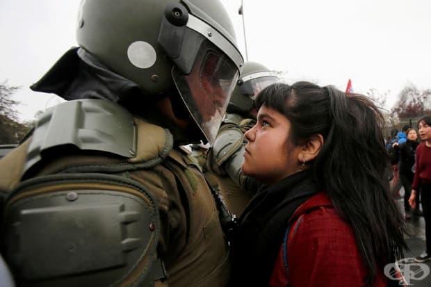 Демонстратор гледа полицай по време на протест, отбелязващ военния преврат от 1973 г. в Сантиаго, Чили.