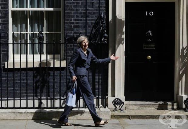 След окончателното заседание на кабинета на Дейвид Камерън, новият премиер Тереза Мей се усмихва на фотографите, вървейки в грешна посока на излизане от Даунинг стрийт 10.
