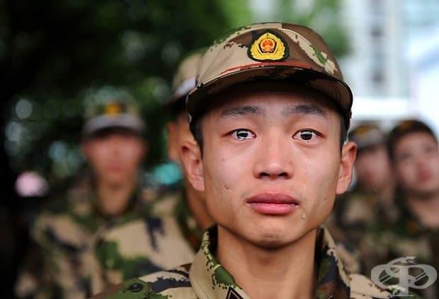 Китайски паравоенен полицай потъва в сълзи преди експедиране.