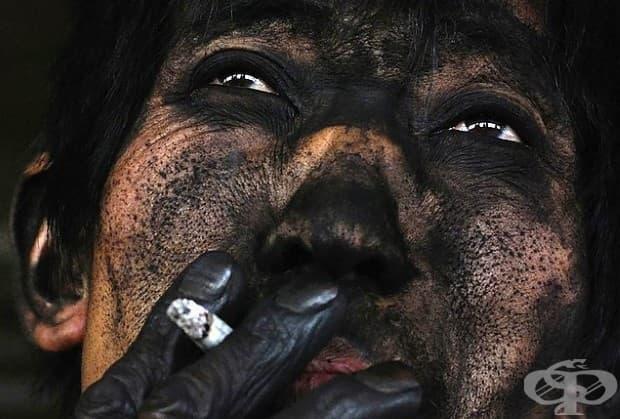 Миньор пуши цигара след приключване на смяната си в покрайнините на Чангзи.