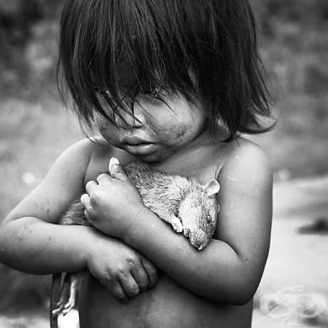 Малко гуаранско момиче стиска здраво умрял плъх.
