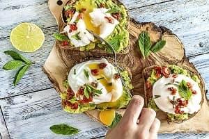 Пълнозърнести филийки с мус от авокадо, сушени домати и яйца